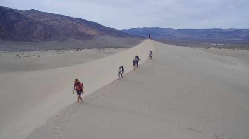 Researchers walk on sand dune in Death Valley